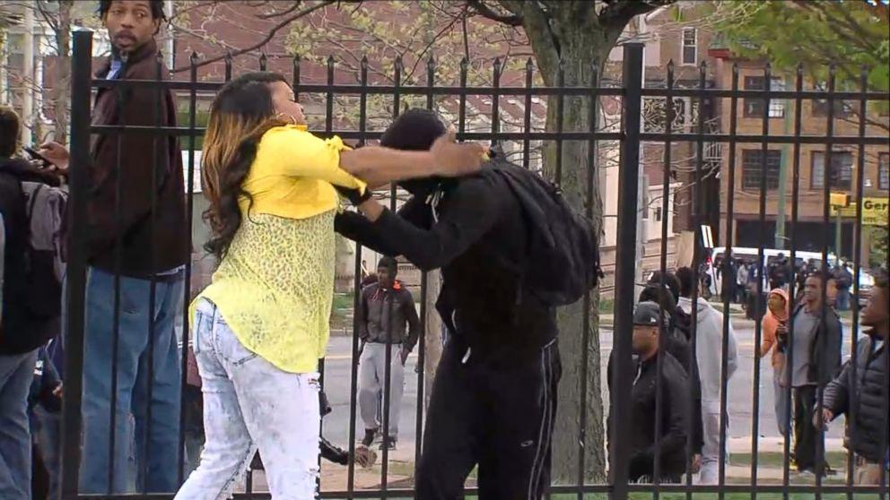 schiaffeggia e trascina via il figlio che lancia pietre alla polizia